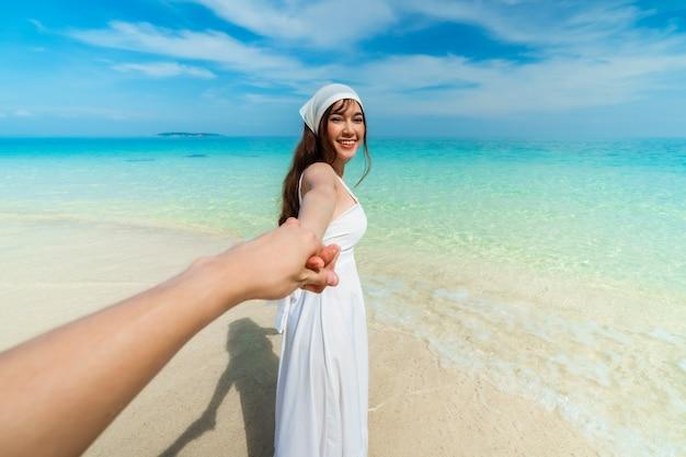 Счастливая женщина в платье, держащая руку парня на морском пляже на острове ко мун норк, районг, таиланд