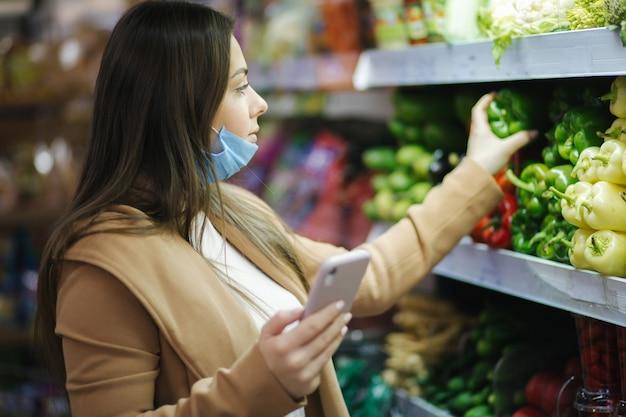 얼굴 마스크에 행복 한 여자는 전화를 잡고 슈퍼마켓에서 야채를 선택합니다. 야채와 함께 서 식료품을 선택하는 아름 다운 젊은 비즈니스 여자. 건강 격리. 코로나 19.