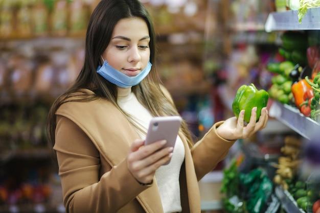 フェイスマスクの幸せな女性は電話を保持し、スーパーマーケットで野菜を選択します。野菜とスタンドで食料品を選ぶ美しい若いビジネス女性。検疫。 covid19。