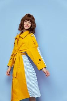 Счастливая женщина в модном пальто с поясом и круглыми пуговицами