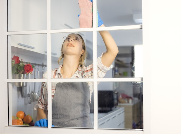 Счастливая женщина в перчатках, чистящих стеклянное окно на домашней кухне. концепция работы по дому.