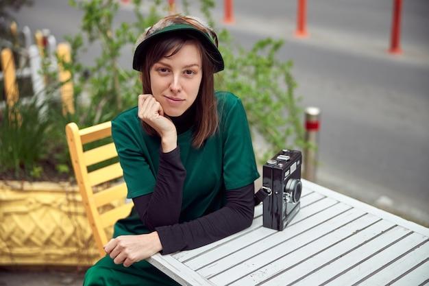 도시의 도시에서 녹색 드레스에 행복한 여자는 카페 근처에 앉아있다
