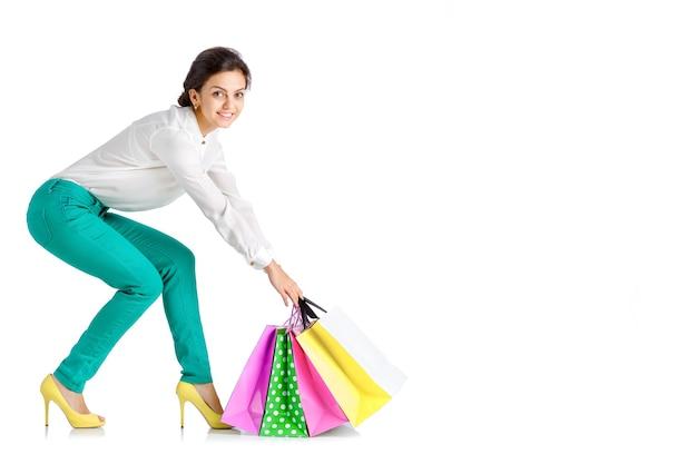 흰색 배경에 고립 된 쇼핑 가방 녹색 바지에 행복 한 여자