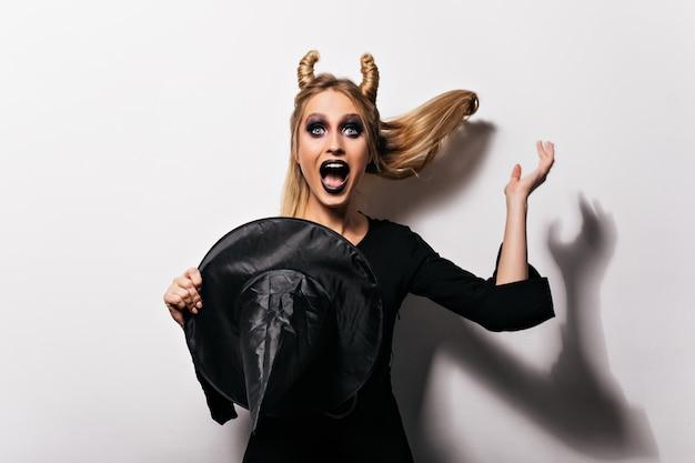 Счастливая женщина в костюме хеллоуина, держащем шляпу ведьмы. фотография изумленной девушки в одежде вампира в помещении.