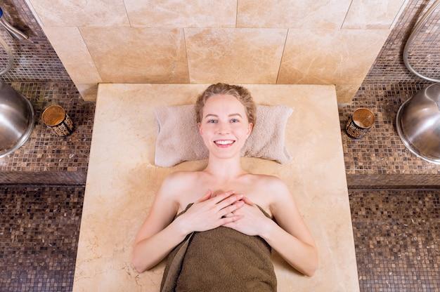 터키 식 목욕탕 또는 터키 식 목욕탕에서 행복 한 여자 휴식