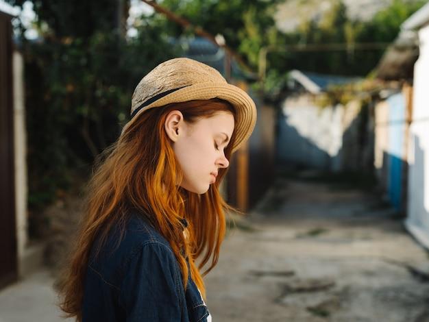 帽子の赤い髪のシャツモデルの田舎で幸せな女性