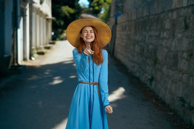 Счастливая женщина в шляпе показывает пальцем в камеру