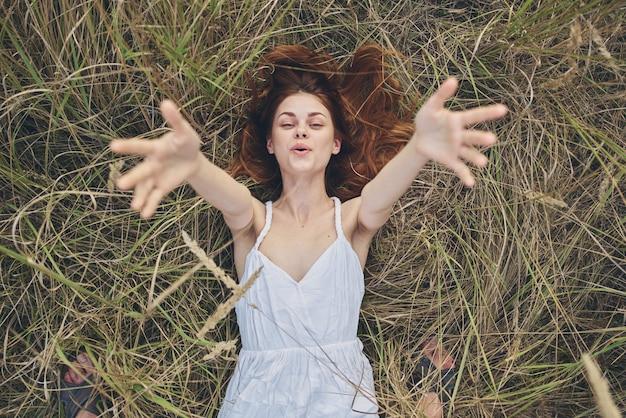 Счастливая женщина в стоге сена протягивает руки вверх и обрезанный вид.