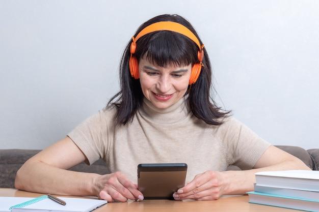 Счастливая женщина в наушниках улыбается, сидя за столом с книгами и слушая музыку или аудиокнигу дома. дистанционное обучение