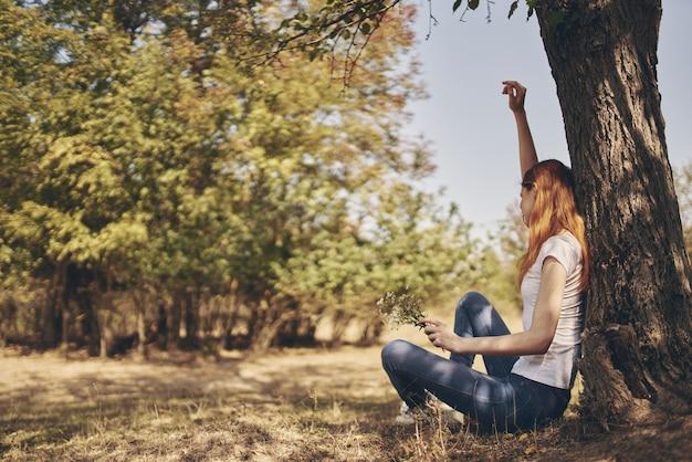 Счастливая женщина в джинсах в футболке сидит возле дерева с поднятыми руками.