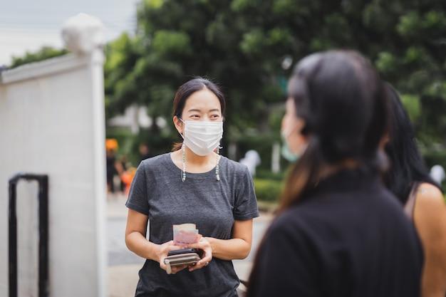 持ち帰り用の食べ物を待っている通りで友人と立っている医療保護マスクの幸せな女性。
