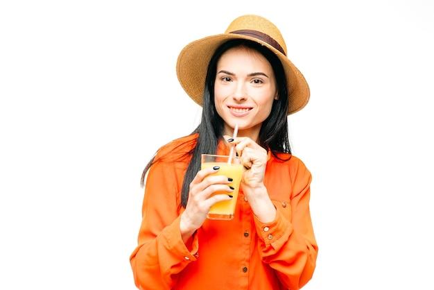 オレンジ色のシャツと麦わら帽子の幸せな女性は、白で絞りたてのジュースを飲みます。