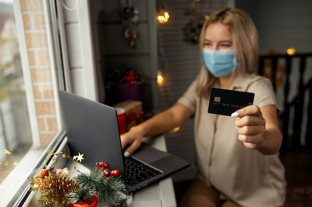 보호 마스크에 행복 한 여자, 은행 카드를 손에 들고 집에서 온라인 쇼핑을 하 고 격리 기간 동안 크리스마스 선물을 구입. 카드에 집중했습니다.