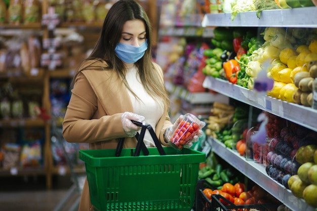 슈퍼마켓에서 식료품에 서있는 동안 신선한 야채를 복용 보호 마스크에 행복 한 여자