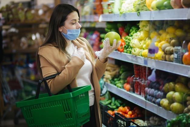 スーパーマーケットの食料品のそばに立っている間新鮮な野菜を取る保護マスクの幸せな女性