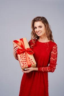 贈り物を保持している赤いドレスの幸せな女性