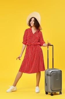 黄色の背景に旅行に行く灰色のスーツケースと赤いドレスの幸せな女性。旅行の概念。