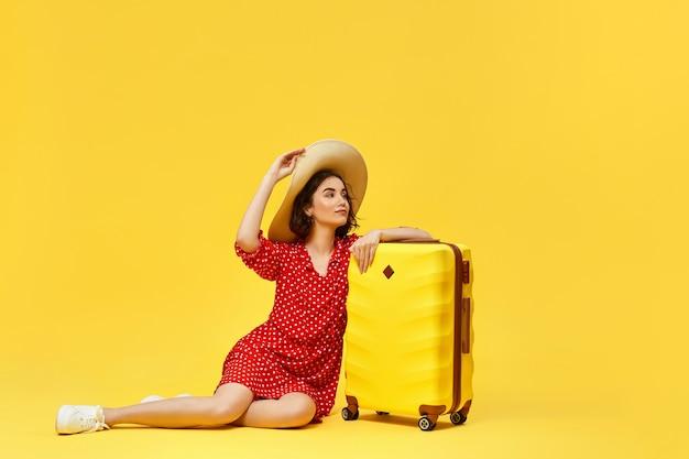 黄色の背景で旅行に行くスーツケースと赤いドレスの幸せな女性。旅行の概念。コピースペース