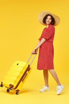 黄色の背景で旅行に行くスーツケースと一緒に歩いて赤いドレスを着た幸せな女性。