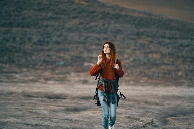 自然の中で休んでいる彼女の背中にバックパックと赤いセーターの幸せな女性