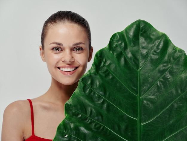 입을 크게 벌리고 녹색 잎 야자수 깨끗한 피부 모델로 웃고 있는 빨간 수영복을 입은 행복한 여성