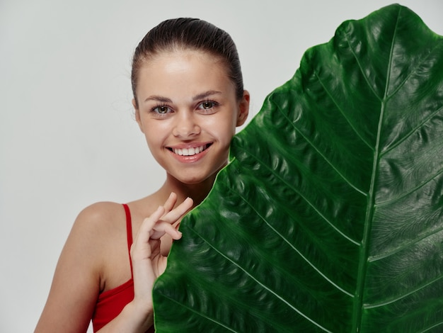 緑の葉と赤い水着で幸せな女性はきれいな肌をキャッチ