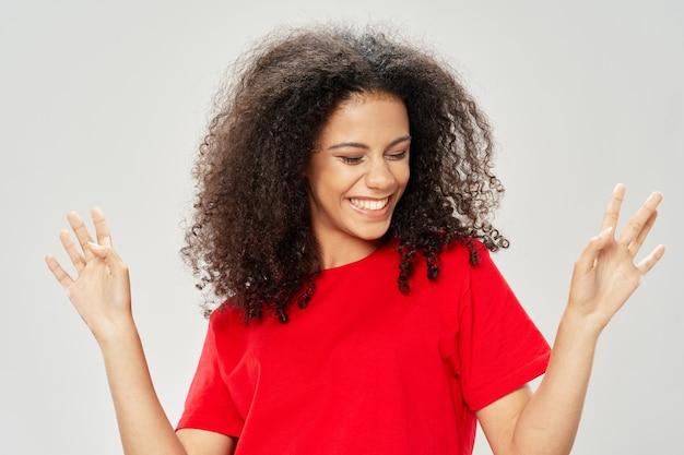 Счастливая женщина в красной футболке, жестикулирующая руками и вьющимися волосами