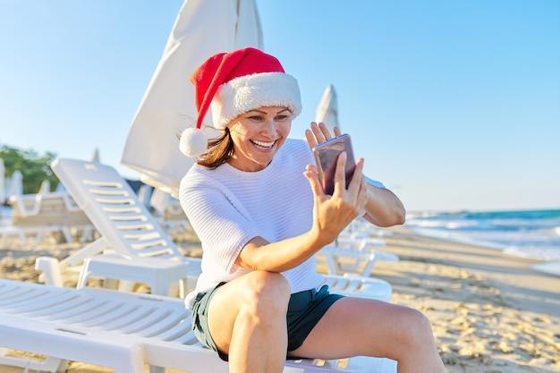Счастливая женщина в новогодней шапке на пляже