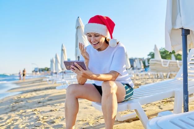 ビーチでサンタの帽子をかぶって幸せな女性