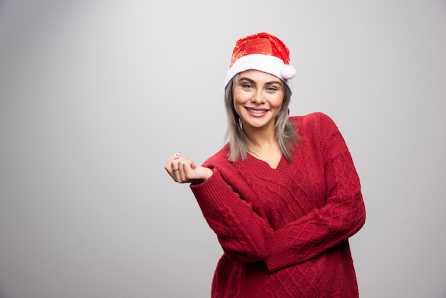 회색 배경에 포즈 산타 모자에 행복 한 여자.