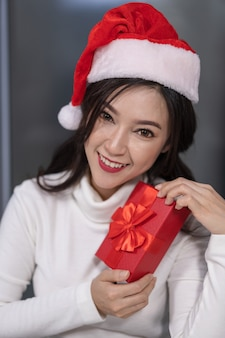 Счастливая женщина в шляпе санта с рождественским подарком