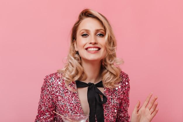 弓と光沢のあるトップの幸せな女性はピンクの壁に笑っています