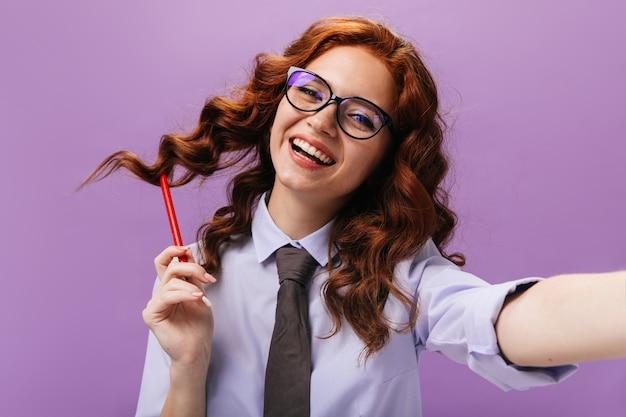紫色の壁で笑っているシャツと眼鏡の幸せな女性