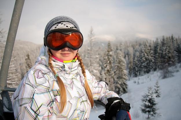 カルパティア山脈のリフトでスキー眼鏡で幸せな女が上昇します。閉じる。冬の自然。大雪が降る。