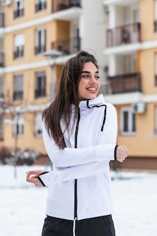 Счастливая женщина в спортивной одежде и с длинными волосами, визжащими зимой. концепция фитнеса снега.