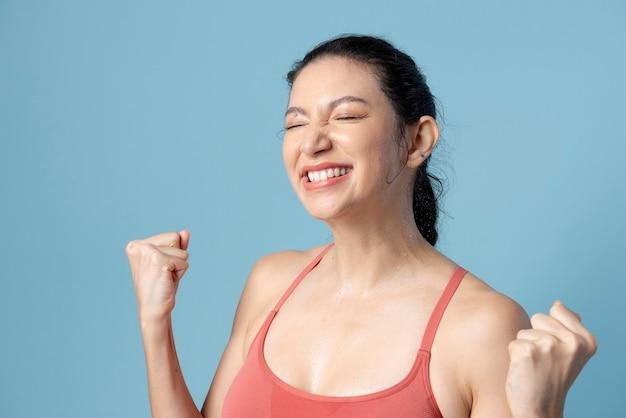 Счастливая женщина в спортивной одежде на синем фоне