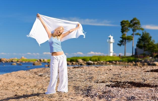 海岸の縞模様のベストで幸せな女性