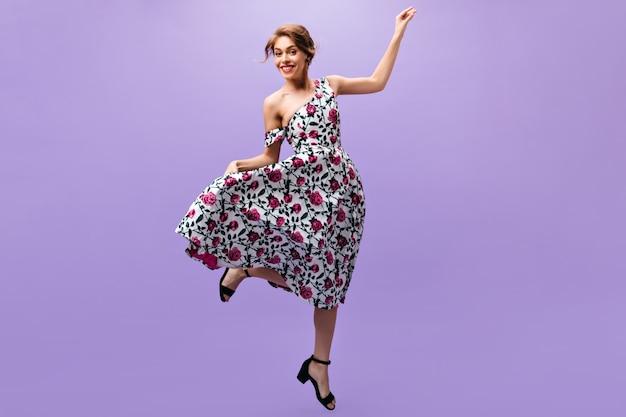 Счастливая женщина в стильном платье скачет на фиолетовом фоне. радостная привлекательная девушка в модном цветочном наряде позирует на изолированном фоне.