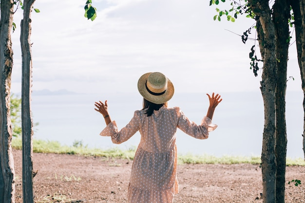 열대 이국적인 전망과 함께 휴가에 여름 귀여운 드레스와 밀짚 모자에 행복한 여자
