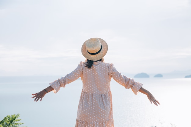 Счастливая женщина в летнем милом платье и соломенной шляпе на отдыхе с тропическими экзотическими видами