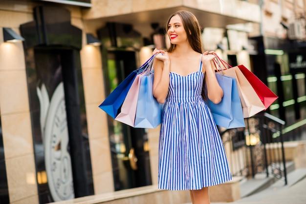 Счастливая женщина в летнем платье позирует с хозяйственными сумками
