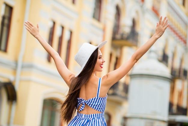 밀 짚 모자와 함께 포즈를 취하는 여름 드레스에 행복 한 여자
