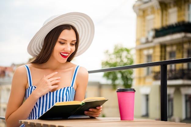 麦わら帽子でポーズをとって夏のドレスで幸せな女性