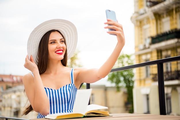 Счастливая женщина в летнем платье позирует в соломенной шляпе