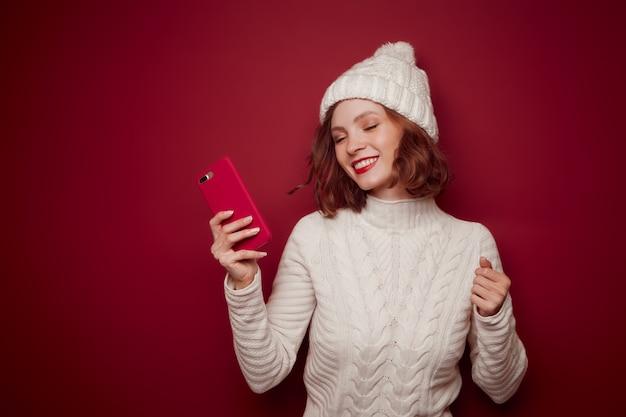 Счастливая женщина в свитере держит телефон