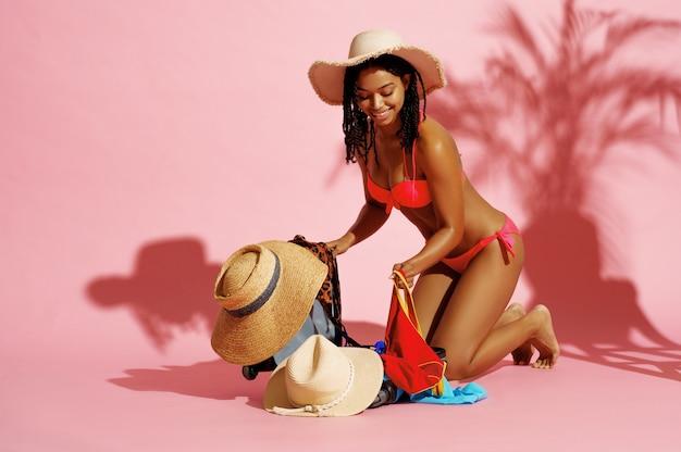 Счастливая женщина в купальнике распаковывает одежду на розовом