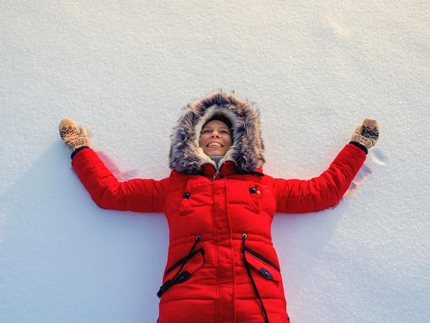 雪の中で幸せな女性。トップフラット俯瞰図。