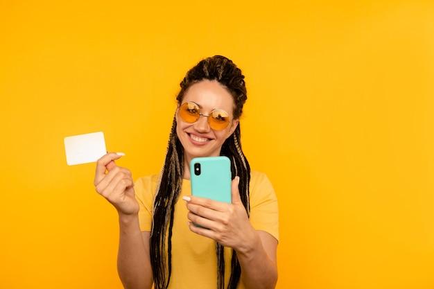 모바일 신용 카드를 들고 노란색 티셔츠에 행복 한 여자.