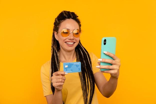 모바일 신용 카드를 들고 노란색 t-shurt에서 행복 한 여자.