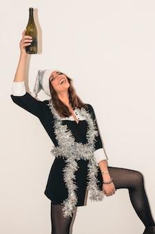 Счастливая женщина в мишуре с бутылкой шампанского